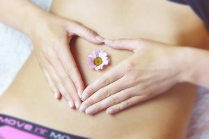 Person with a flower in the navel with their hands around in in the shape of a heart over the abdominal brain region.