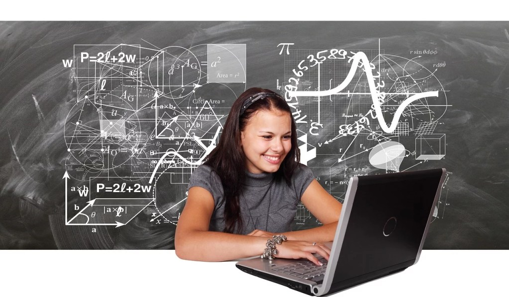 a student on a computer with a chalk board behind them