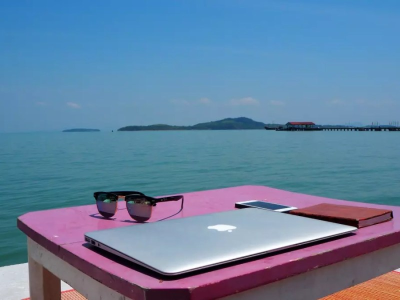 remote work pink table sunglasses laptop