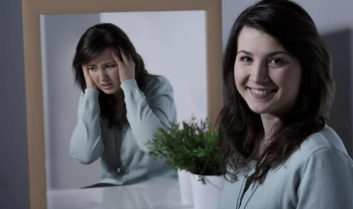 Mujer frente al espejo, viendose refleja como una mujer conmal humor, pero en realidad se encuentra sonriendo