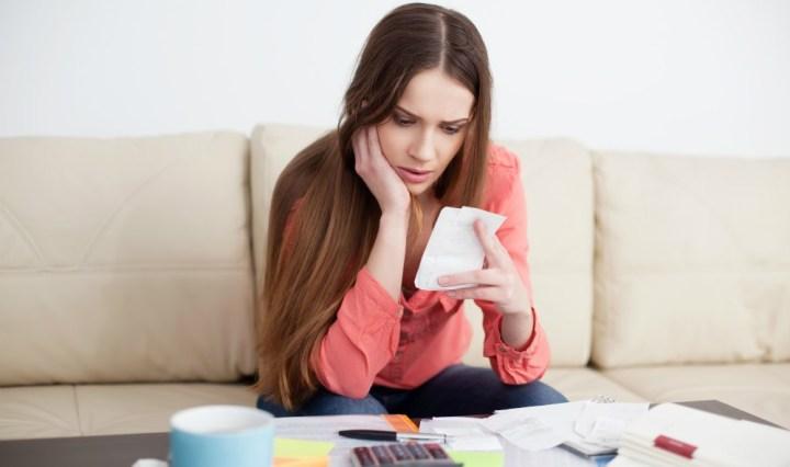 Jóven calculando sus gastos para observar si puede conseguir su independencia financiera en su vida