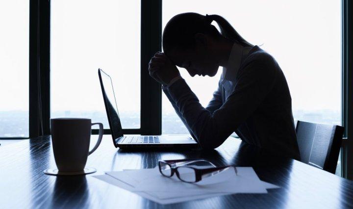 Mujer sufriendo en la oficina problemas psicosomaticos, sin saber que poder hacer