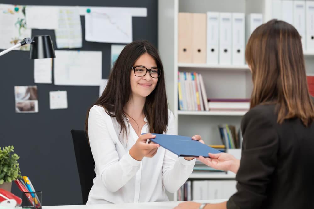 Mujer entregando su hoja de vida a un coach profesional para ayudarla a encontrar trabajo