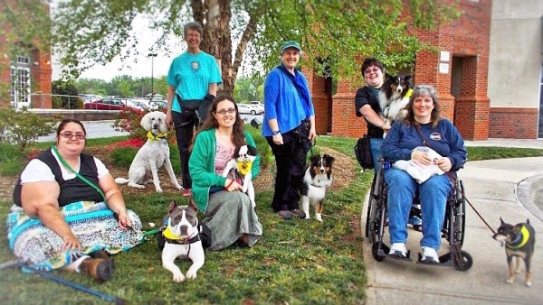 Six community members with service dogs face the camera and smile.