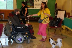 Bearded man in power wheelchair hand-holds and dances with a long-haired woman in a bright yellow blouse and bright salmon skirt, with a leash around her body and a small, vested, black and white dog next to her. A kelly green backdrop with a PSDP banner is in the background.