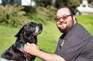 A dark-haired, bearded man wearing glasses and a gray t-shirt smiles at the camera as he pets his large, black dog on the neck while the dog looks up in apparent pleasure with closed eyes