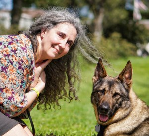 A smiling white woman with long, curly gray hair kneels and poses facing the camera with a lying German Shepherd with grass in the background.