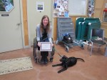 Inside a room with wire dog fencing and PVC-framed dog platforms stacked against the wall, a woman in a wheelchair smiles at the camera as she holds a certificate with both hands. A short, green leash appears to be attached either to her wrist or her chair, and it leads to a black lab puppy lying on the faded terra cotta colored floor.