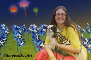 Graphic with text. Picture: Smiling woman with long brown hair crouching on grass holding small black and white dog wearing a yellow vest, with blue and silver pinwheels around them; the distant background is digitally drawn as if three cartoon fireworks have exploded. Text in lower left: #ServiceDogArt