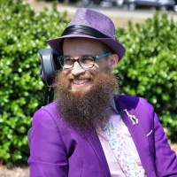 The bust of a smiling man with a large beard, sitting in a power wheelchair and looking left with bright greenery in the background. The man wear a purple straw fedora, a purple blazer, pink dress shirt, a pink-background tie with flowers of different colors, and a multi-color giraffe lapel pin. The sun shines brightly down on him.