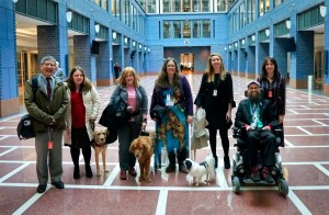 Seven disability advocates pose for a picture in an expansive central indoor area at the US Department of Transportation building in Washington, DC on November 25, 2019.
