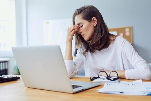 εργαζόμενη γυναίκα με άγχος που πιάνει το κεφάλι της μπροστά από λάπτοπ