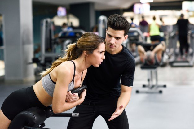 woman in the gym with trainer