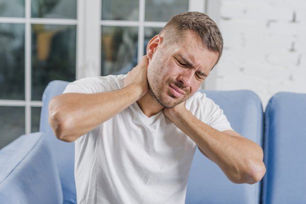 man sitting on sofa with neck pain