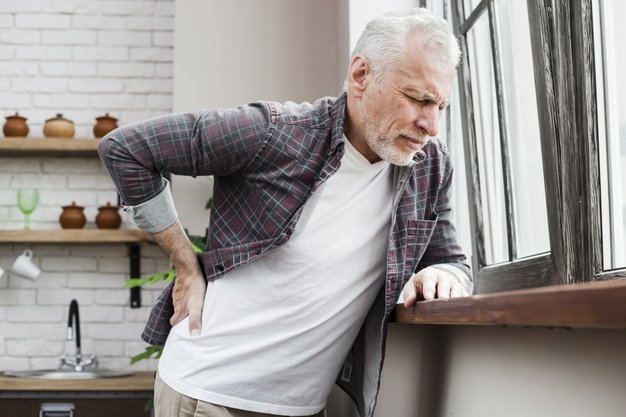 man in pain standing by the window