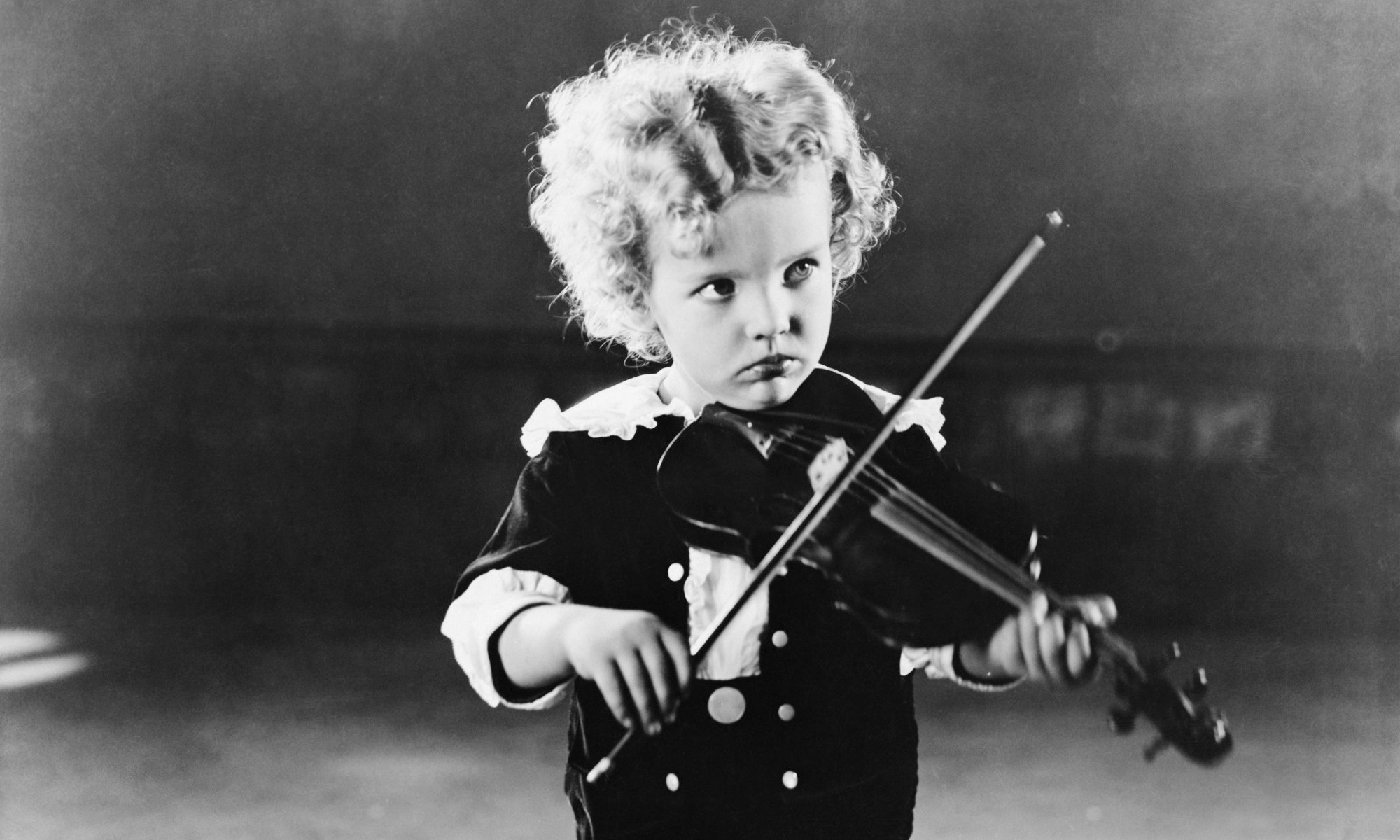 Little boy playing violin. What vs how can make a big difference in learning and development