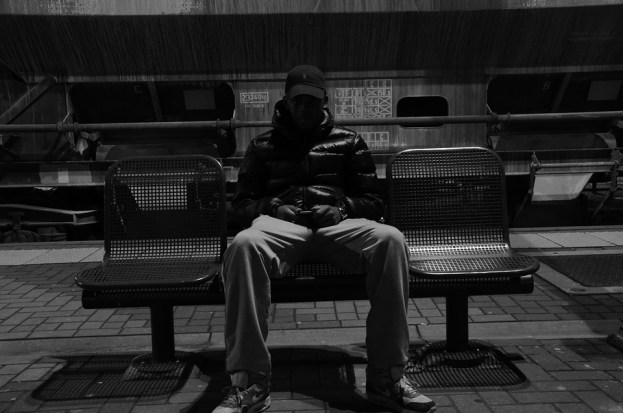 man wearing jacket sitting in a bench