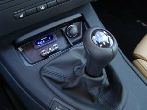 A dongle on top of that plug will touch the drivers hand when he shifts gears.