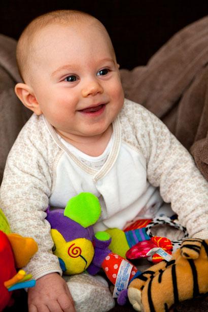 Sonriente bebé con los juguetes