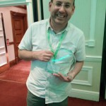 Showing off the CILIP Wales Library Champion of the Year Award, wearing remarkably casual clothing.