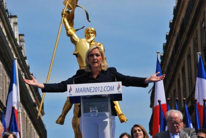 Far-Right French Politician Marine Le Pen at a rally in front of a statue of Joan of Arc.