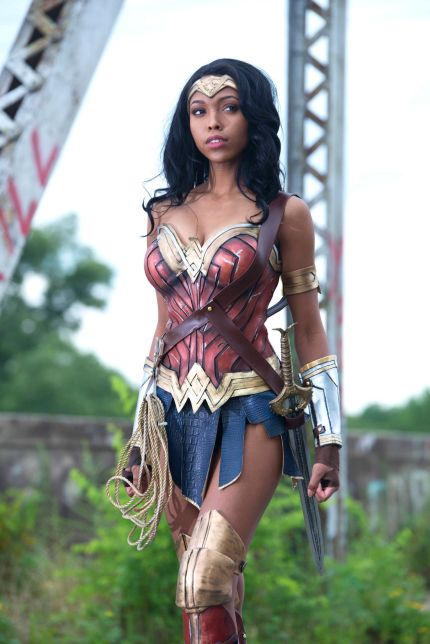 A black woman dressed as Wonder Woman in a red, gold, and blue leather bustier and skirt.