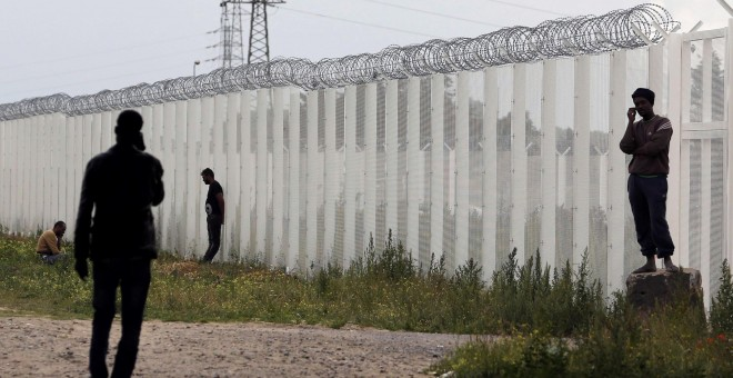 Varios inmigrantes llaman por teléfono cerca de una cerca con alambre de púas, junto al campamento improvisado llamado