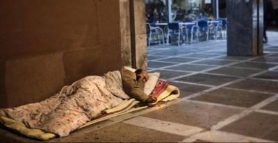 Un hombre sin techo duerme en la acera, junto a una cafetería. EFE