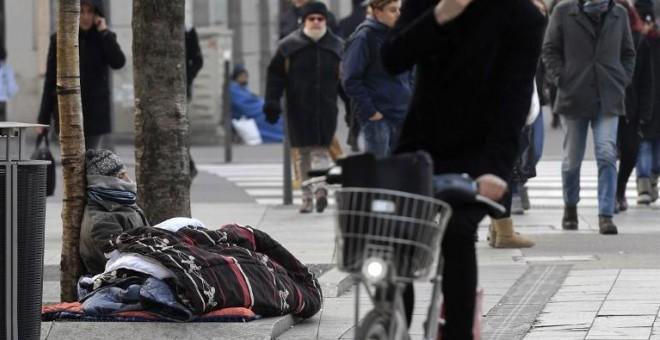 Una persona sin hogar dormita en la calle, en una imagen de archivo. AFP