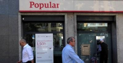 Varios transeuntes pasan junto a una oficina del Banco Popular en Madrid. REUTERS/Juan Medin