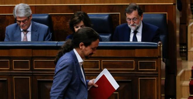 El líder de Podemos, Pablo Iglesias, pasa por delante del presidente del Gobierno, Mariano Rajoy, sentado en su escaño, durante la moción de censura. REUTERS/Juan Medina