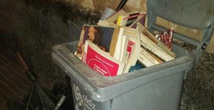 Montones de libros en un contenedor de basura