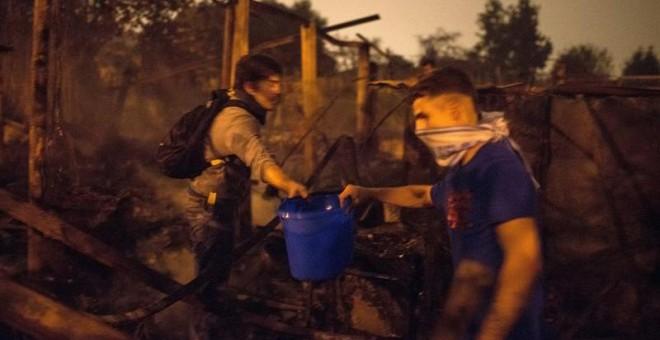 Ciudadanos ayudan a sofocar con cubos de agua uno de los focos declarados en el centro de la ciudad de Vigo. - BRAIS LORENZO