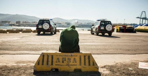 Un migrante descansa en el puerto de Algeciras, custodiado por la Guardia Civil tras ser rescatado por Salvamento Marítimo junto a potros migrantes a bordo de una patera.- JAIRO VARGAS
