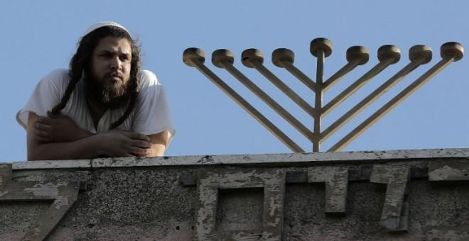 Un colono judío en la azotea de una antigua casa de una familia palestina en Jerusalén Este. - AFP