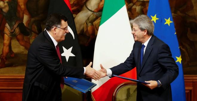 El primer ministro italiano Paolo Gentiloni (D) y su homólogo libio Fayez al-Sarraj se dan la mano después de firmar un acuerdo bilateral durante una reunión en Palacio de Chigi en Roma, Italia, el 2 de febrero de 2017.- REUTERS / Tony Gentil