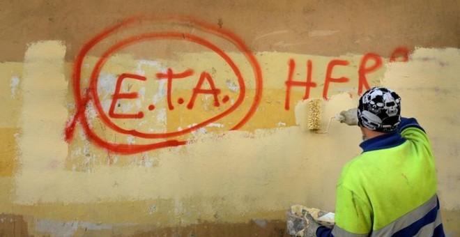 Un trabajador municipal borra un graffiti en el que se podía leer 'ETA, la gente está contigo' en el pueblo vasco de Guernica, el día después que la banda terrorista anuncaria el cese de sus actividades en 2011.REUTERS/Vincent West
