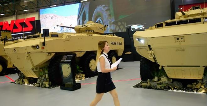 Una mujer pasa junto a un par de vehículos blindados en la Feria Internacioanl de Industria de Defensa, en Estambul. AFP/Yasin Akgul