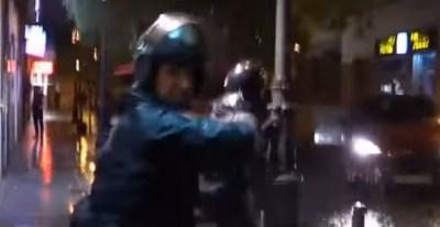 Momento en el que un agente de policía golpea la mano de otro otro agente que se cruza en su camino