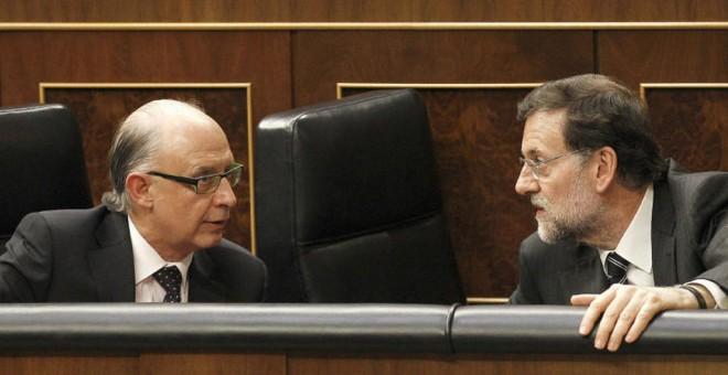 El presidente del Gobierno, Mariano Rajoy, conversa con el ministro de Hacienda, Cristóbal Montoro, en sus escaños de la bancada azul del Congreso de los Diputados. EFE