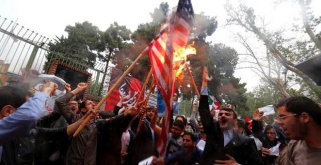Un grupo de iraníes quema una bandera estadounidense mientras participan en una protesta contra Estados Unidos frente a la antigua embajada estadounidense en Teherán (Irán). / EFE