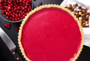 cranberries in a bowl next to a large tart with red filling and spices