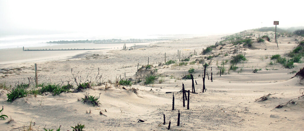 a beach with a broken wooden fence
