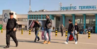 Flughafen Kabul: Ein Gruppe junger Männer verlässt in Begleitung von Polizisten das Flughafengebäude. Einige der in Deutschland abgelehnten Asylbewerber versuchen an diesem Tag Ende Februar 2017 ihr Gesicht zu verbergen. (Foto: pa/Jawad)