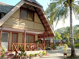 Photo of two-story cottage with wooden porch railing and coconut tree opposite its front door at Puerto Beach Resort