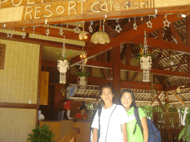 Photo of two ladies wearing t-shirts and jeans each with a backpack standing at entrance to Puerto Beach Resort Cafe and Grill