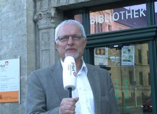 Mann vor Gebäudeeingang spricht ins Mikrofon.