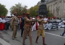 Angehörige der Volksgruppe der Herero und Nama laufen mit Transparenten durch die Berliner Innenstadt.
