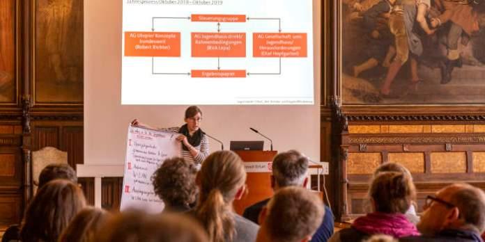 Junge Frau am Rednerpult vor Leinwandpräsentation redet vor Publikum und hält ein Plakat hoch