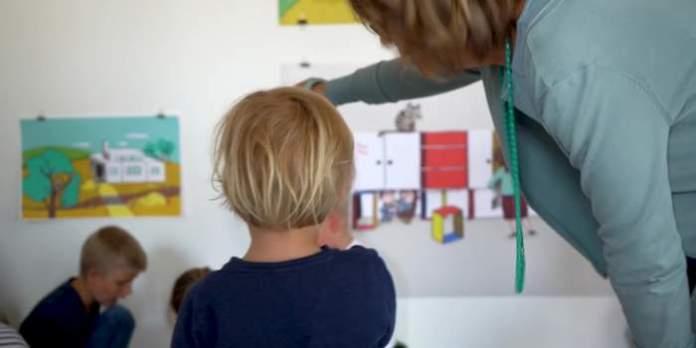 Ein Kind steht vor einer Wand mit Bildern